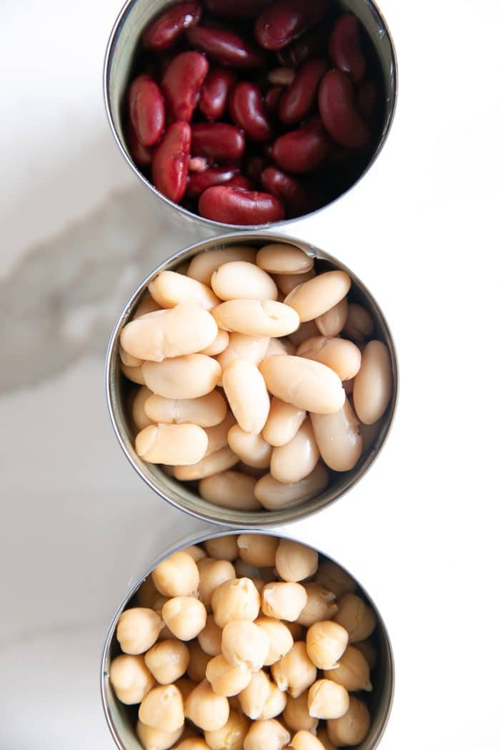 Overhead image of three open cans of beans.