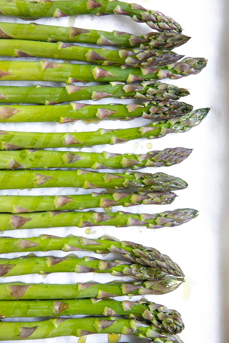 Asparagus in a single layer on a baking sheet.