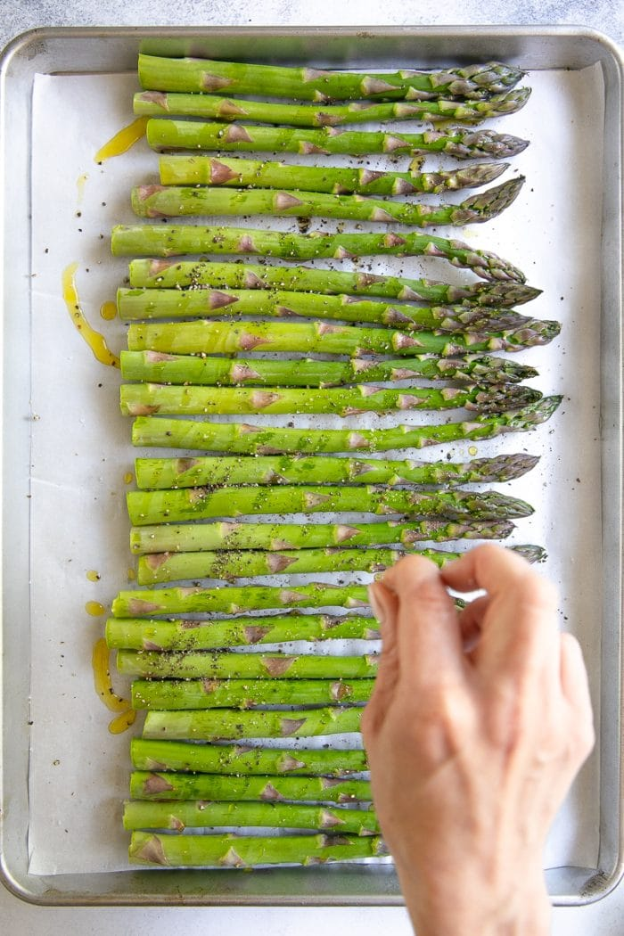 Seasoning a tray of asparagus before baking.