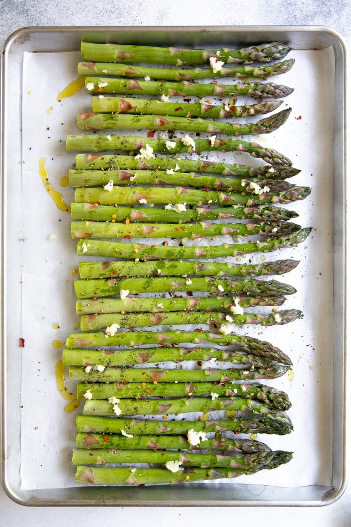 Asparagus seasoned with salt, pepper, and fresh garlic before roasting.