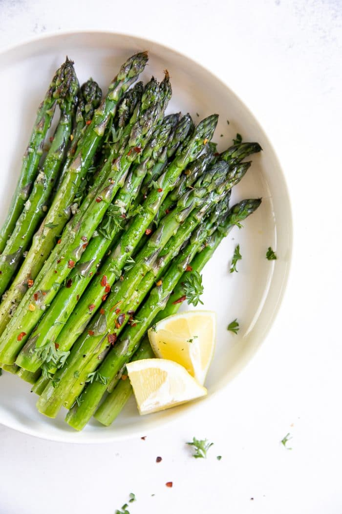 Roasted asparagus in a large flat white serving dish garnished with parsley and served with lemon.
