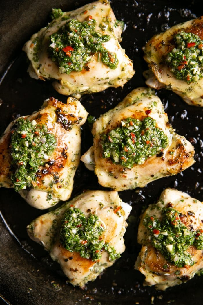 Chimichurri chicken thighs topped with homemade chimichurri sauce.