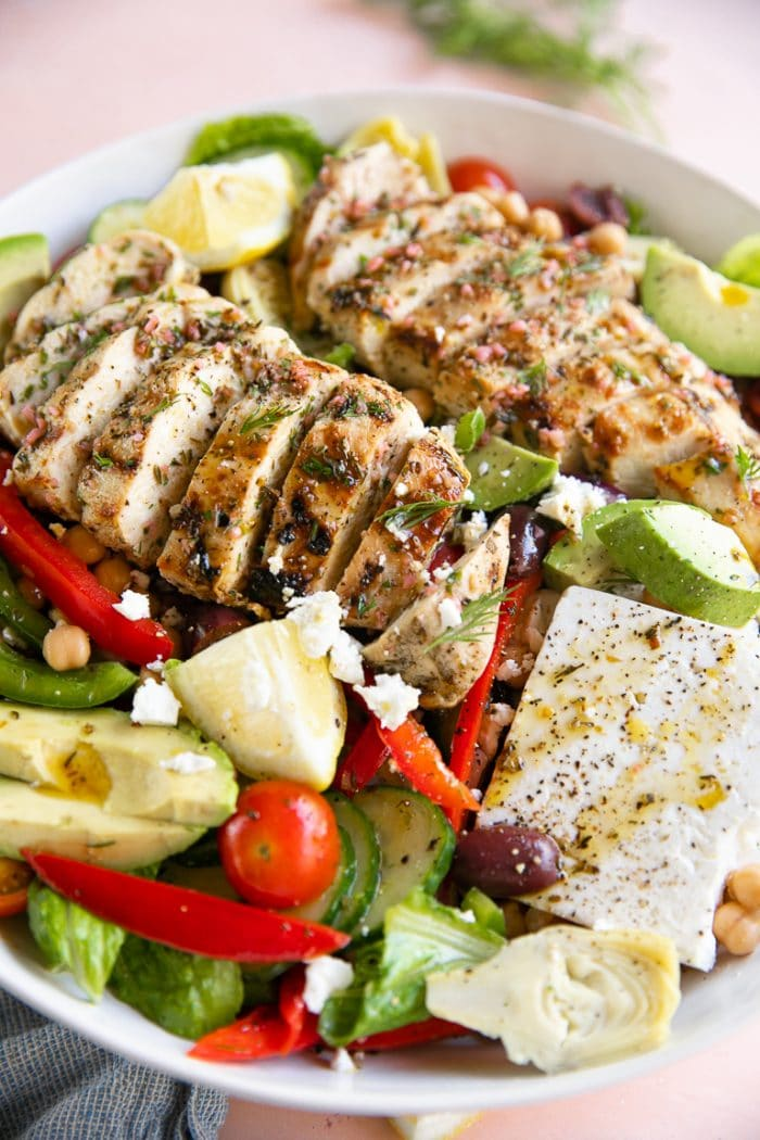 Large white serving bowl filled with lettuce, avocado, feta cheese, bell pepper, olives, and grilled Greek chicken.