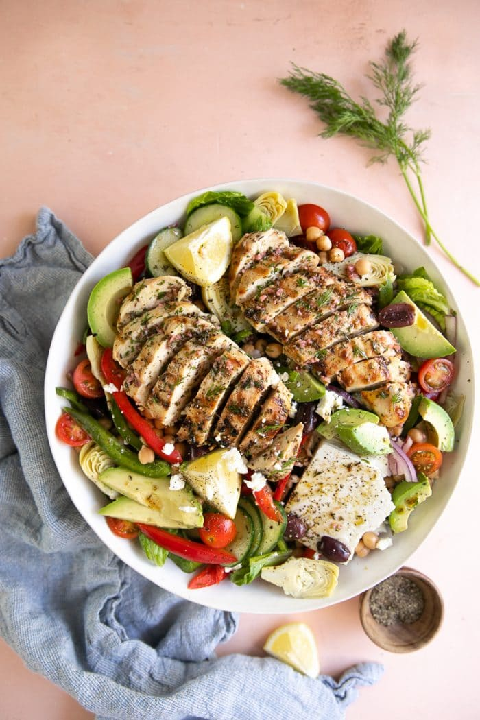 Large salad bowl topped with grilled Greek marinated chicken, feta cheese, and vegetables.