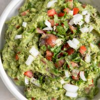 Overhead image of guacamole in a white serving bowl garnished with chopped white onion and tomato.