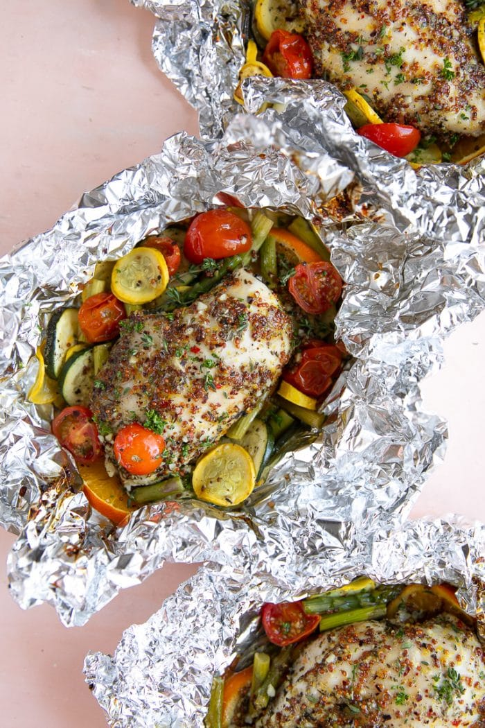 Three foil packets with honey dijon chicken and vegetables.