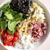 Large white bowl filled with artichokes, mozzarella, salami, cherry tomatoes, fresh spinach, olives, and pasta noodles.
