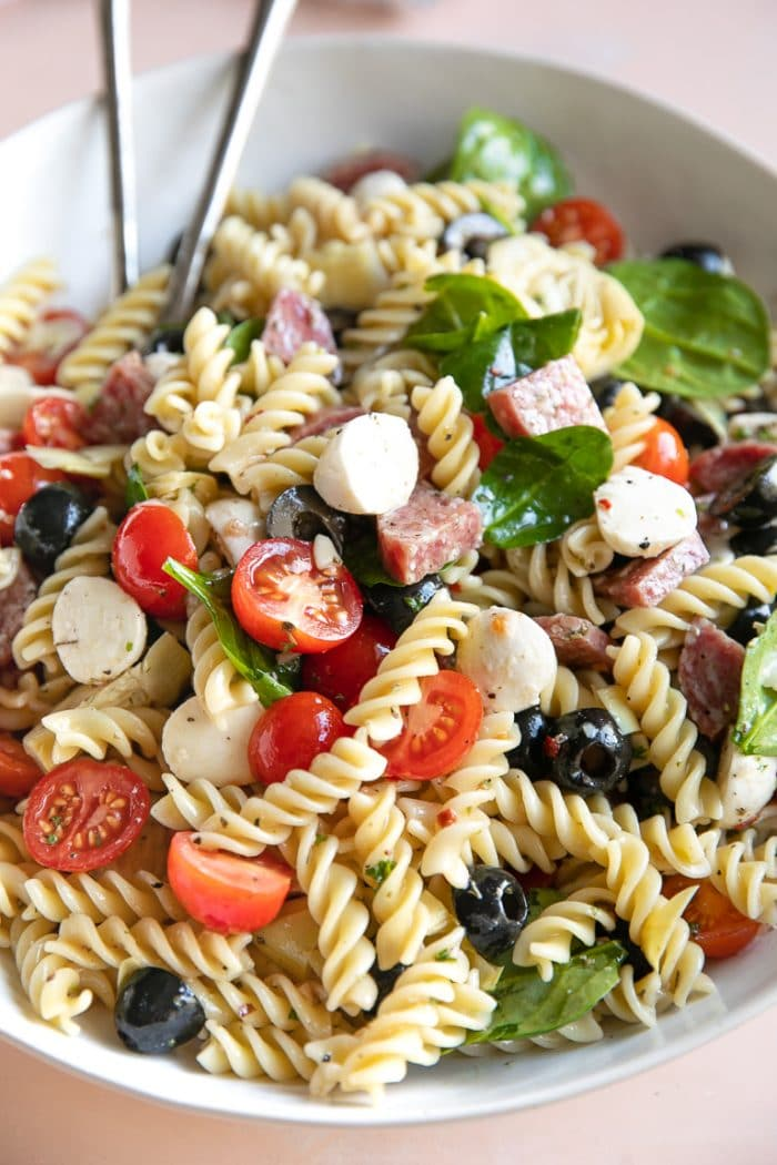 Pasta salad with black olives, salami, spinach, cherry tomatoes, pearl mozzarella.