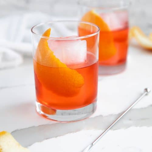 Two Negroni cocktails in a rocks glass garnished with orange peel.