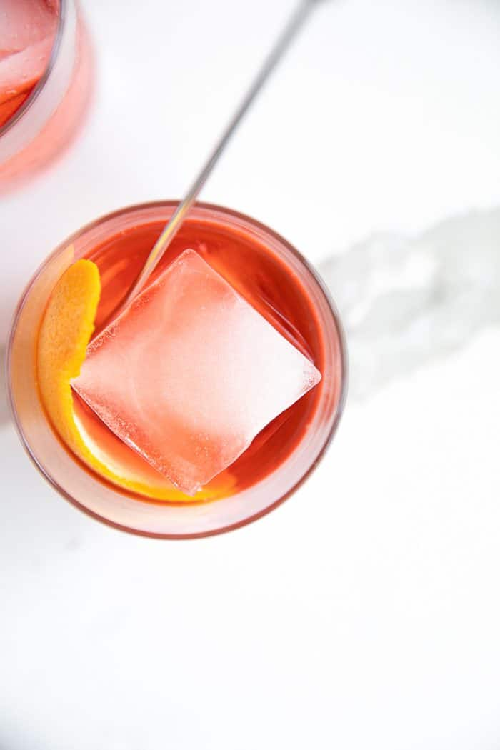 Overhead image of a negroni served in a rocks glass with a single large square ice cube and orange peel.