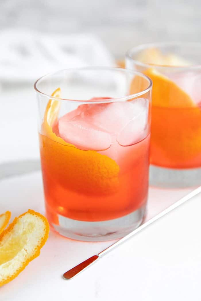 Rocks glass filled with prepared negroni cocktail garnished with an orange slice.