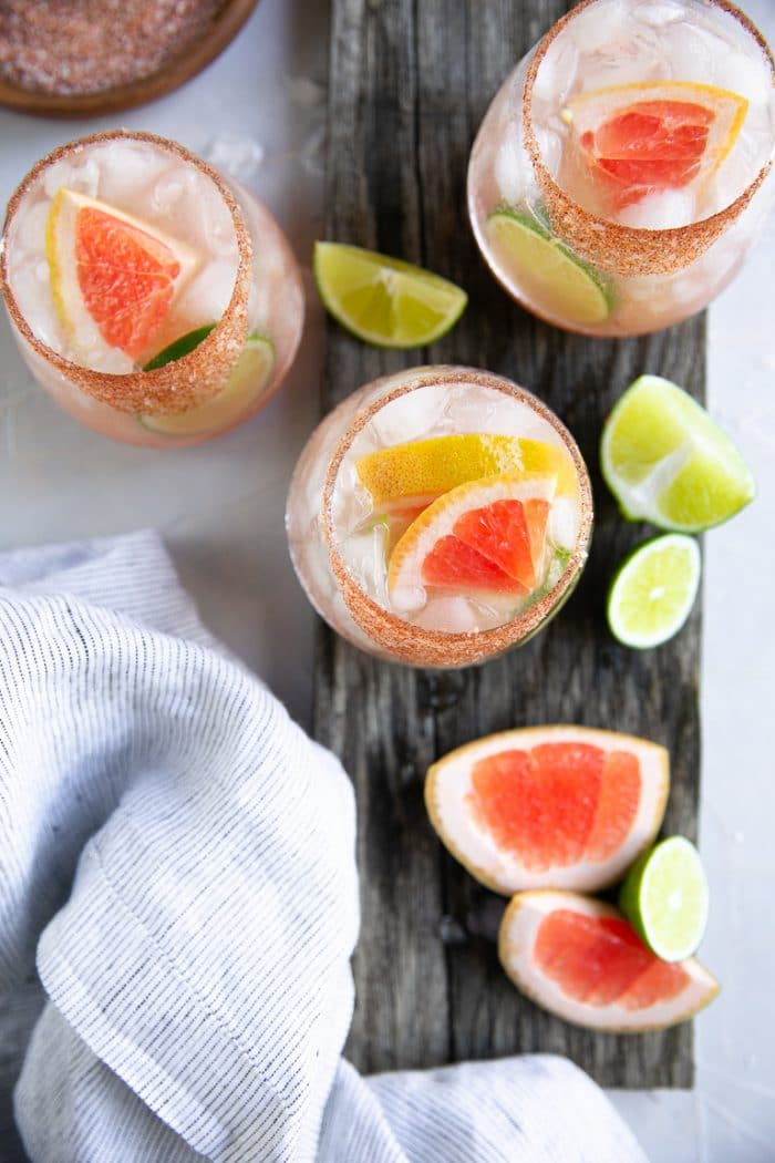 Overhead image of 3 palomas garnished with fresh lime and grapefruit wedges.