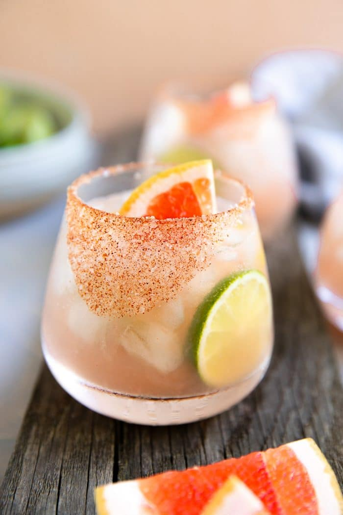 Paloma cocktail served with a chili salt rim and garnished with lime and fresh grapefruit.