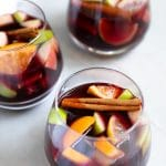 Three glasses of sangria made with red wine, oranges, lemon, apples, and cinnamon stick.