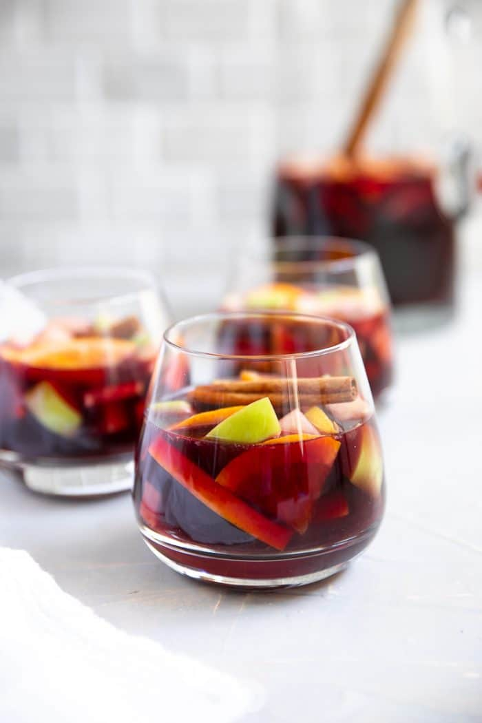 Three glasses and a pitcher of classic red wine sangria.