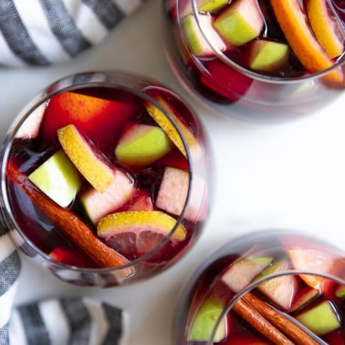 Overhead image of three glasses filled with red wine sangria.