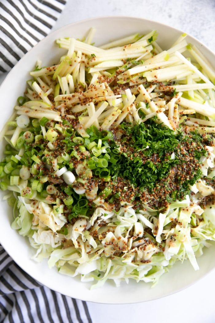 Shredded cabbage, apples, green onion in a large white mixing bowl drizzled with a light vinaigrette and topped with chopped parsley.