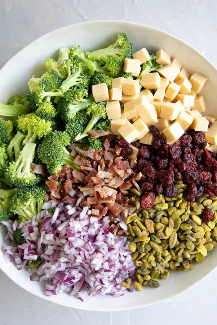 Large white mixing bowl filled with broccoli florets, dried cranberries, small cubes of smoked gouda cheese, diced red onion, crumbled bacon, and pistachios.