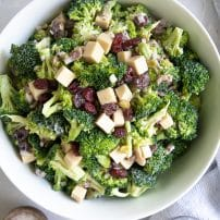Large bowl filled with mixed together broccoli salad with creamy mayo dressing, bacon, and cranberries..