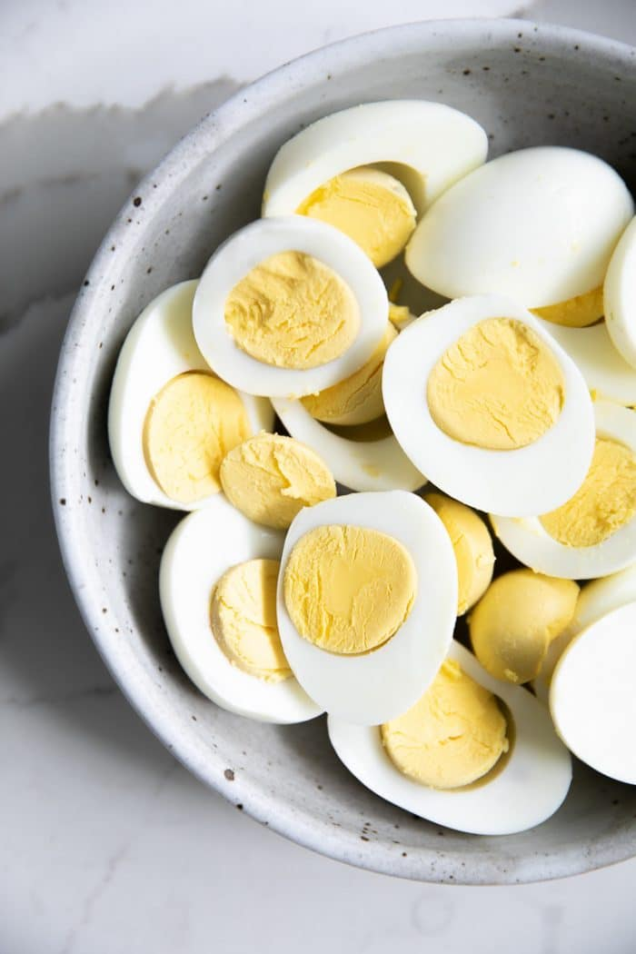 Bowl filled with peeled and halved hard boiled eggs.