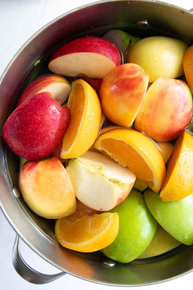 Different types of apples sliced and placed in a large pot with water.