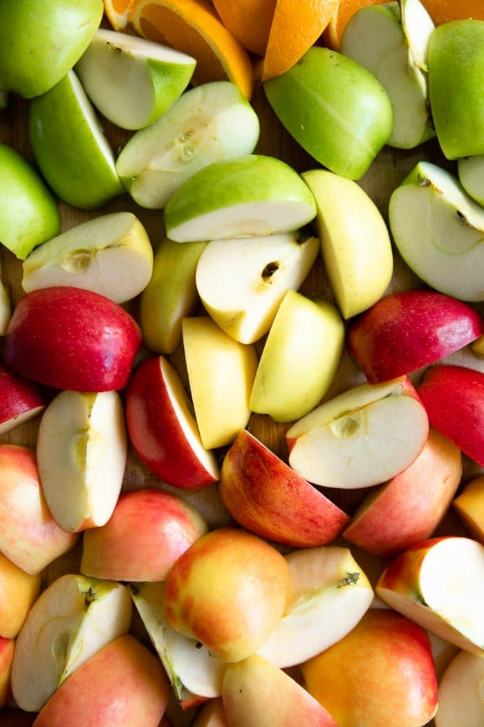 Different types of sliced apples quartered and layed out on a large cutting board.