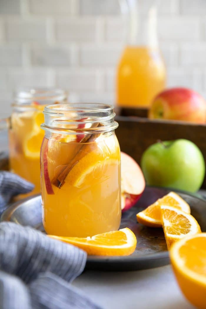 Mason jar filled with warm homemade apple cider garnished with sliced apples, oranges, and cinnamon stick.