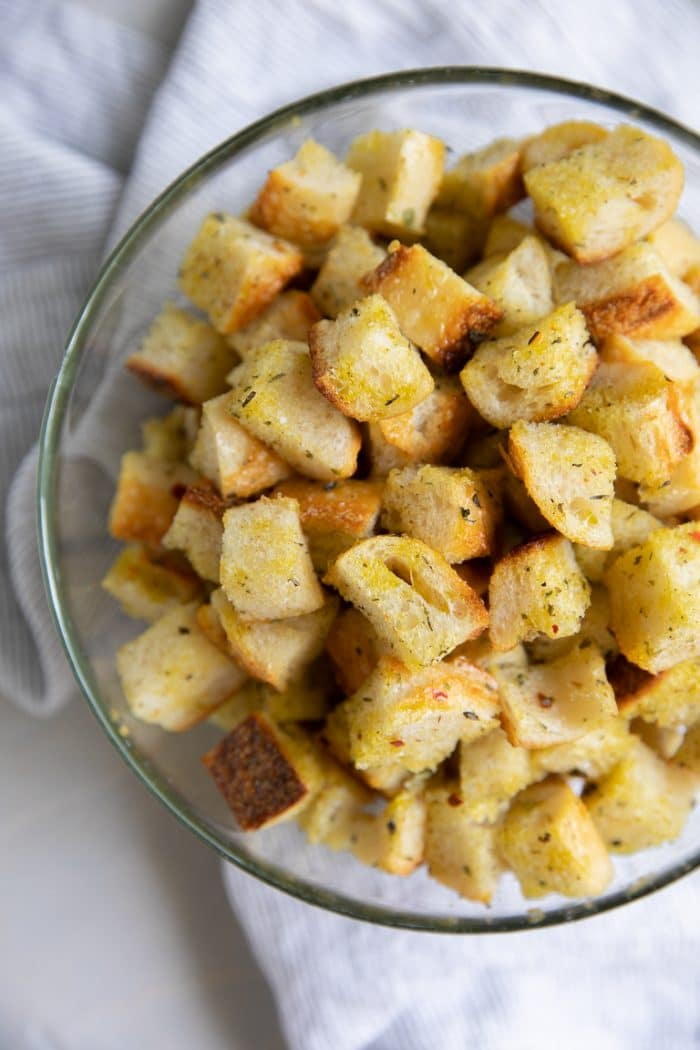 Large glass mixing bowl filled with cubes of fresh bread tossed in olive oil, salt, pepper, and Italian seasoning.