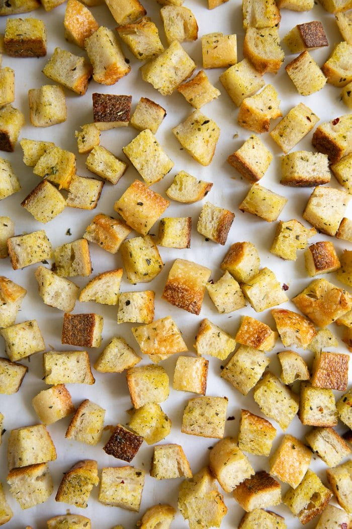 Chopped cubes of bread tossed in olive oil, salt, pepper, and Italian seasoning, spread over a large baking sheet.