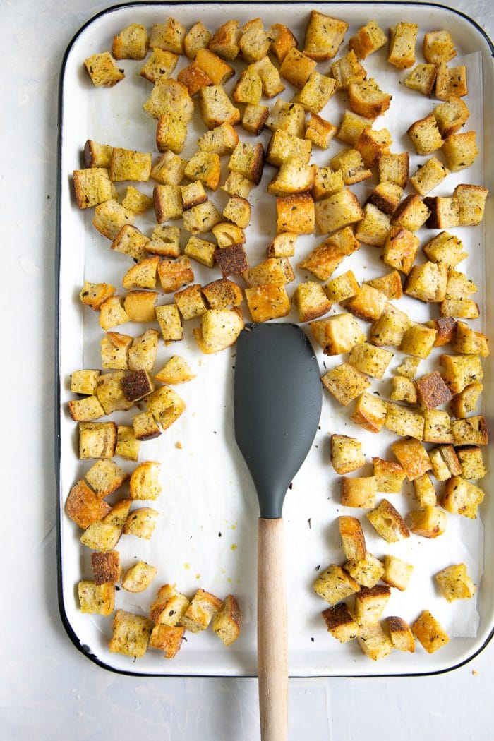 Large white baking sheet filled with homemade toasted croutons.