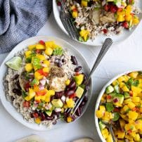 Overhead image of two plates filled with Jamaican rice and peas, Jerk cod, and topped with mango avocado salsa.