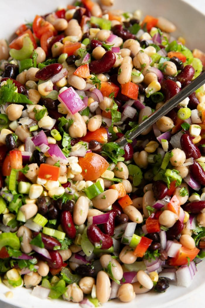 Large white mixing bowl filled with black beans, cannellini beans, kidney beans, corn, tomatoes, red onion, green onion, bell pepper, and cumin.
