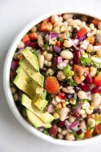 Overhead image of loaded Mexican bean salad topped with sliced avocado.