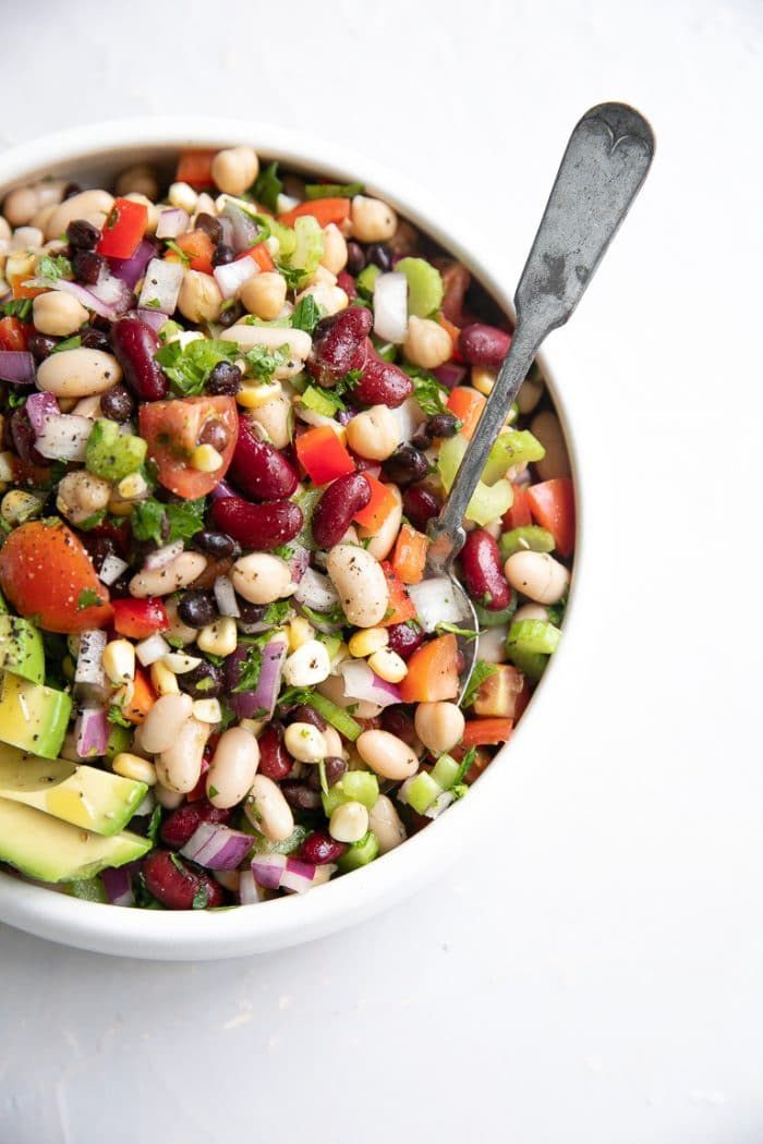 White serving bowl filled with mixed canned beans, bell pepper, cilantro, onion, tomatoes, corn, and avocado.
