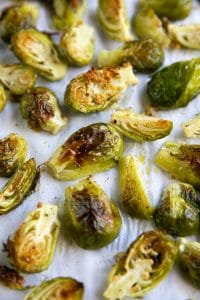 Baking sheet covered with parchment paper and perfectly charred and roasted Brussels sprouts.