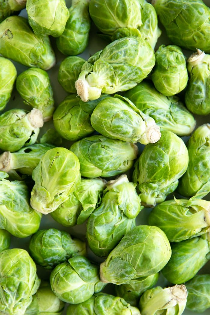 Overhead image of a pile of raw whole Brussels sprouts.