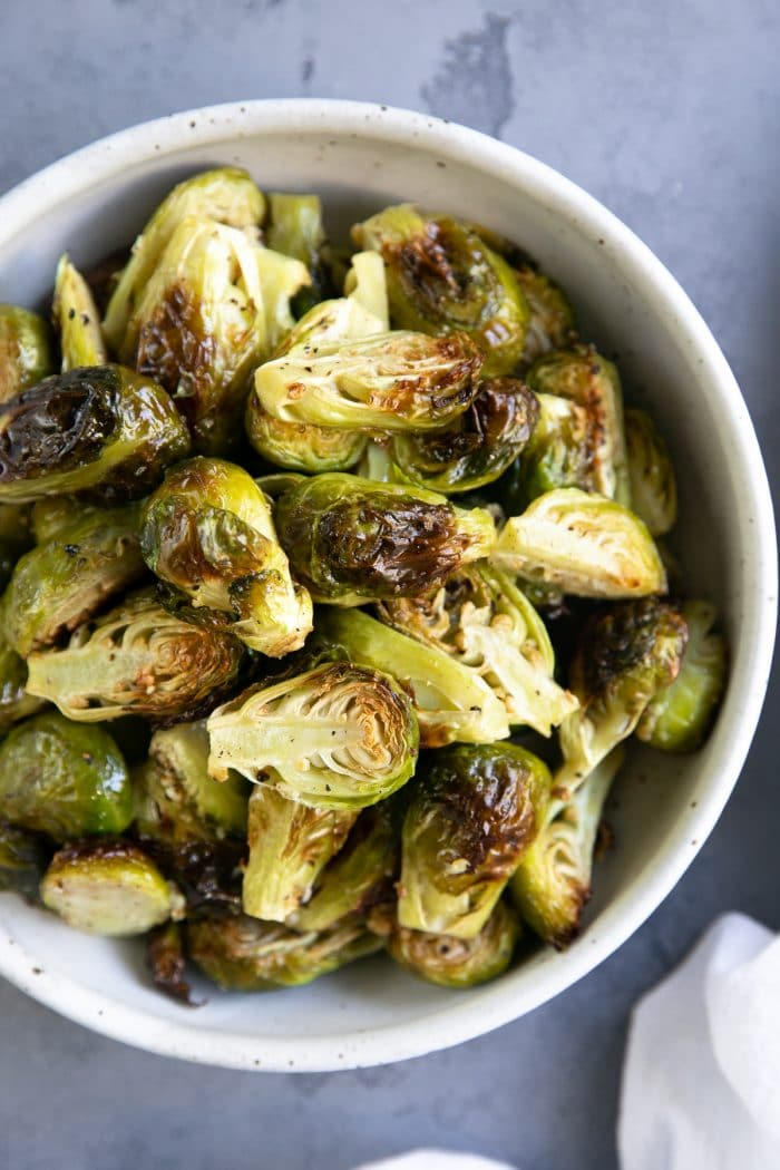 White bowl filled with garlic roasted Brussels sprouts.