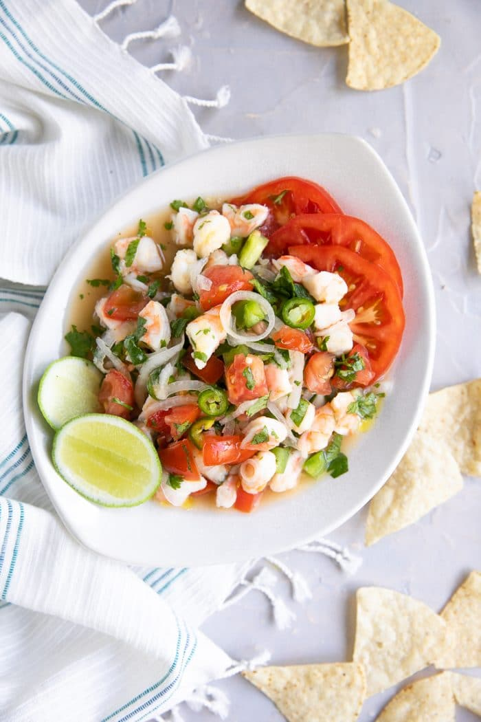 Shrimp Ceviche served in a white bowl and garnished with fresh sliced tomatoes, lime, and tortilla chips.