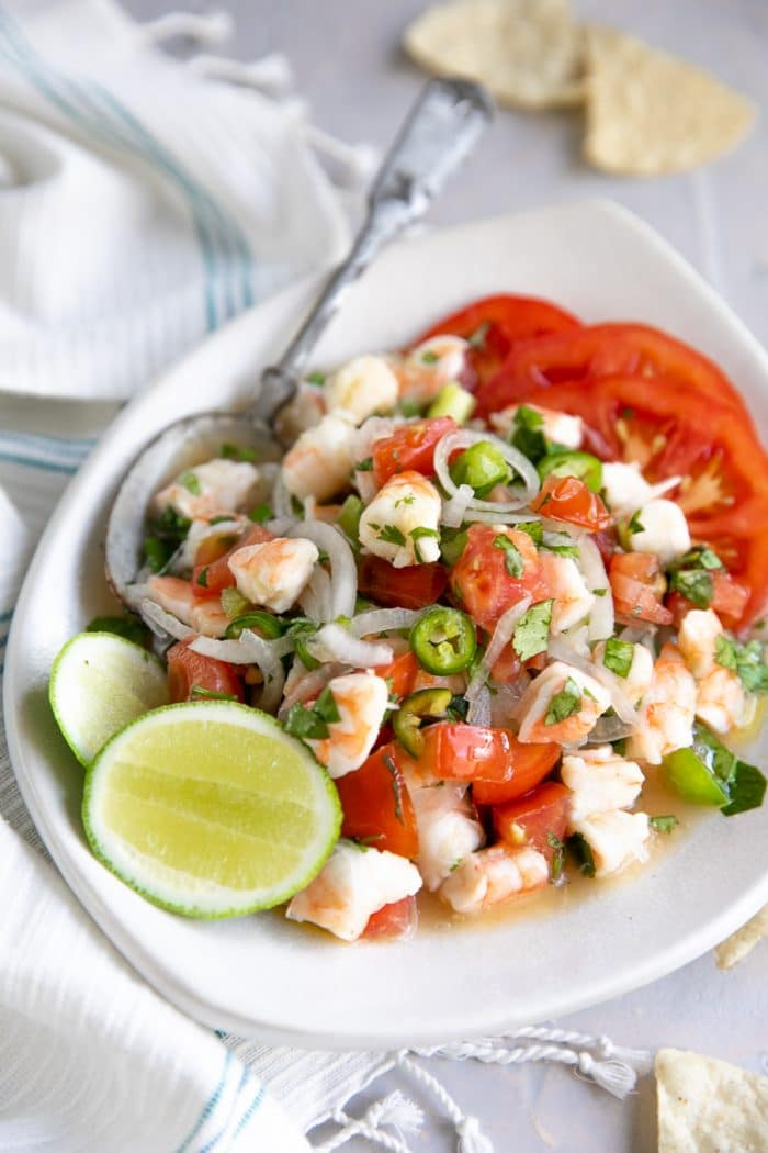 Shrimp ceviche made with onions, tomatoes, bell pepper, lime juice, and cilantro on a white serving plate with sliced tomatoes and fresh lime wedges..
