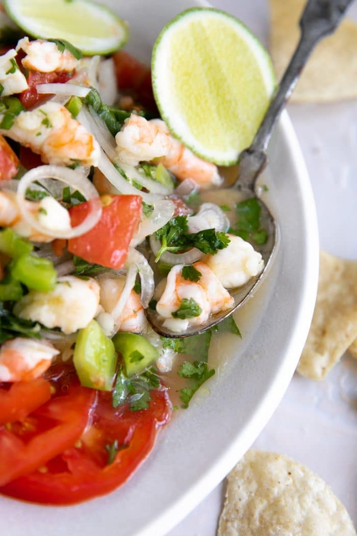 Spoon resting in a white dish filled with fresh shrimp ceviche.
