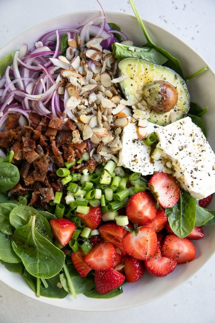Large white salad bowl filled with spinach, strawberries, bacon, red onion, feta, green onion, slivered almonds, and green onions.