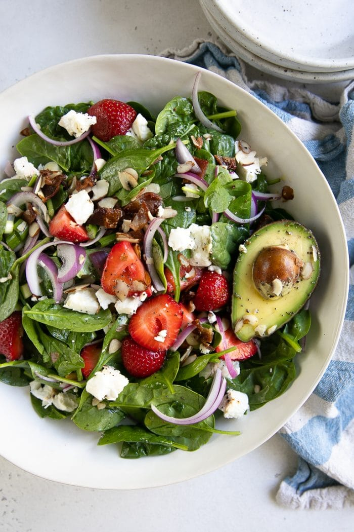 Large white salad bowl filled with tossed together spinach, strawberries, bacon, red onion, feta, green onion, slivered almonds, and green onions.