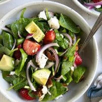 SIngle serving salad bowl filled with strawberry spinach salad.