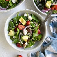Three single serving salad bowls filled with strawberry spinach salad and drizzled with lime vinaigrette.