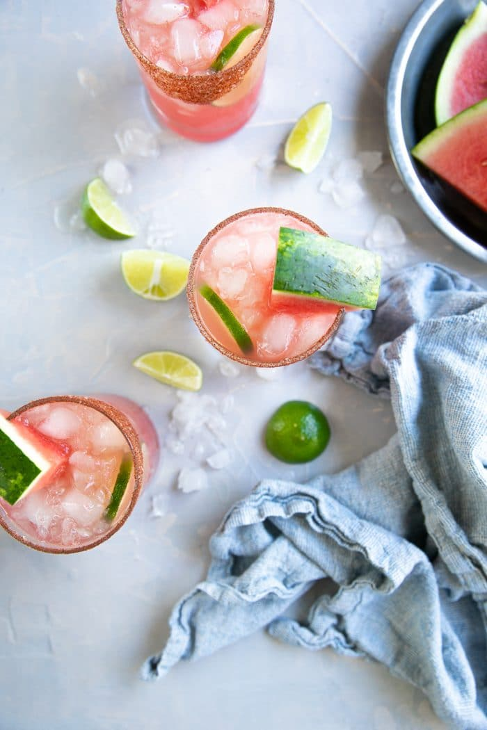 Looking down at two ice cold watermelon margaritas garnished with fresh lime and sliced watermelon.