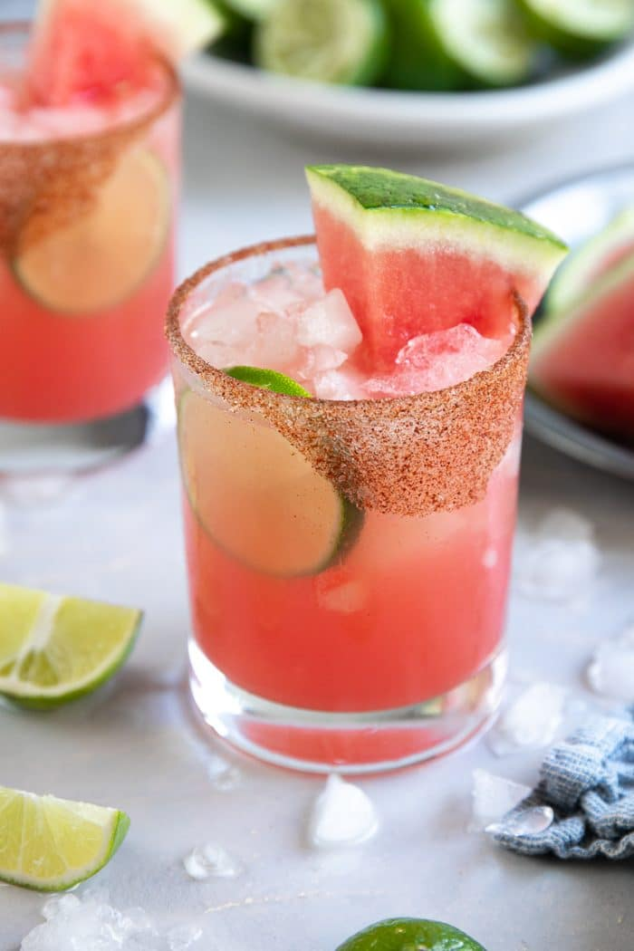 Watermelon margarita in a rocks glass with a chili salt rim.