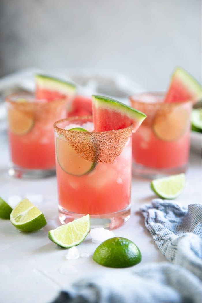 Three iced watermelon margaritas in rocks glasses garnished with fresh lime wheels and sliced watermelon.