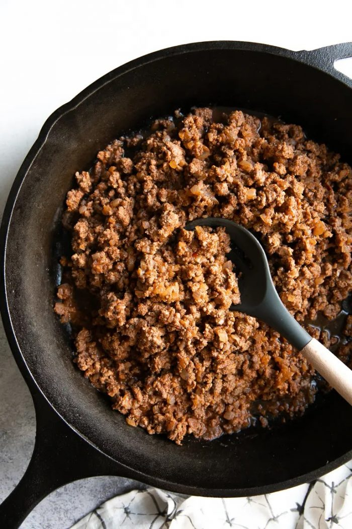 Cast iron skillet filled with cooked ground beef taco meat.