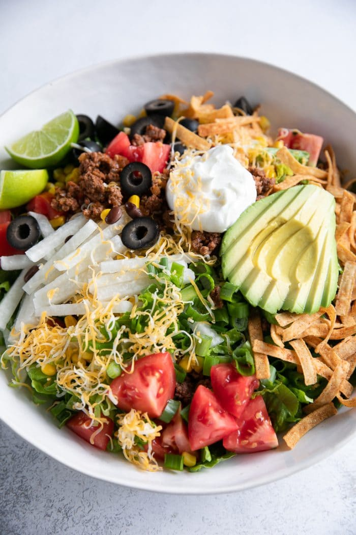 Large white bowl filled with beef taco salad topped with shredded cheese, avocado, olives, tomatoes, and sour cream.