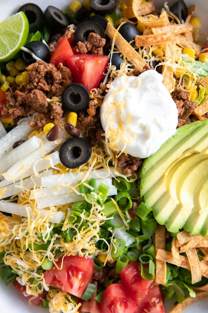 Close up image of taco salad made with ground beef, avocado, cheese, tortilla strips, tomatoes, sour cream, avocado.